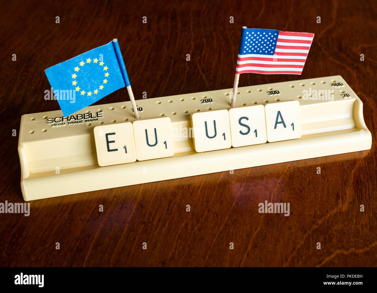 Scrabble letters spelling EU and USA with American and European Union flags on mahogany background to illustrate nation, trade and negotiation concept - Stock Image