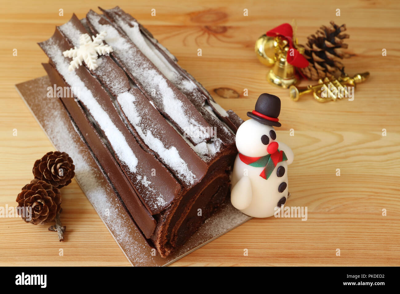Buche de Noel or Chocolate Yule Log Cake with a Cute Snowman Marzipan and Dry Pine Cones, Christmas Ornament on Wooden Table Stock Photo