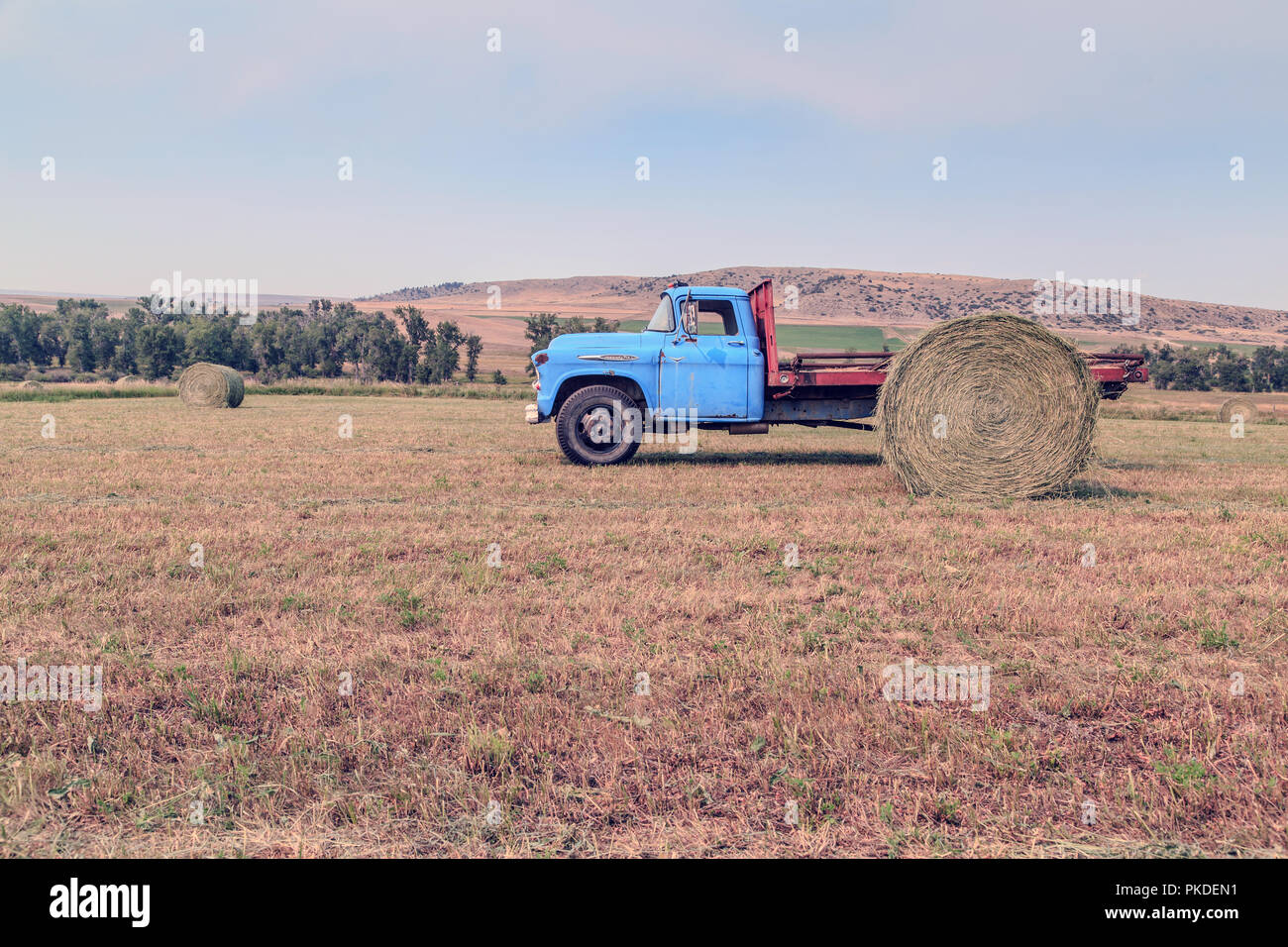 Hay bales and a vintage farm truck in the town of Fishtale, Montana. - Stock Image