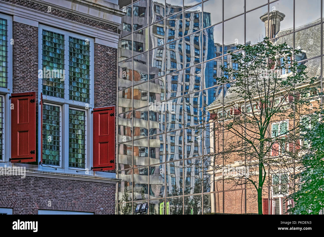 Rotterdam, The Netherlands, September 9, 2017: The brick facade of 17th century Schielandshuis reflects in the shiny glass facade of a nearby office t Stock Photo