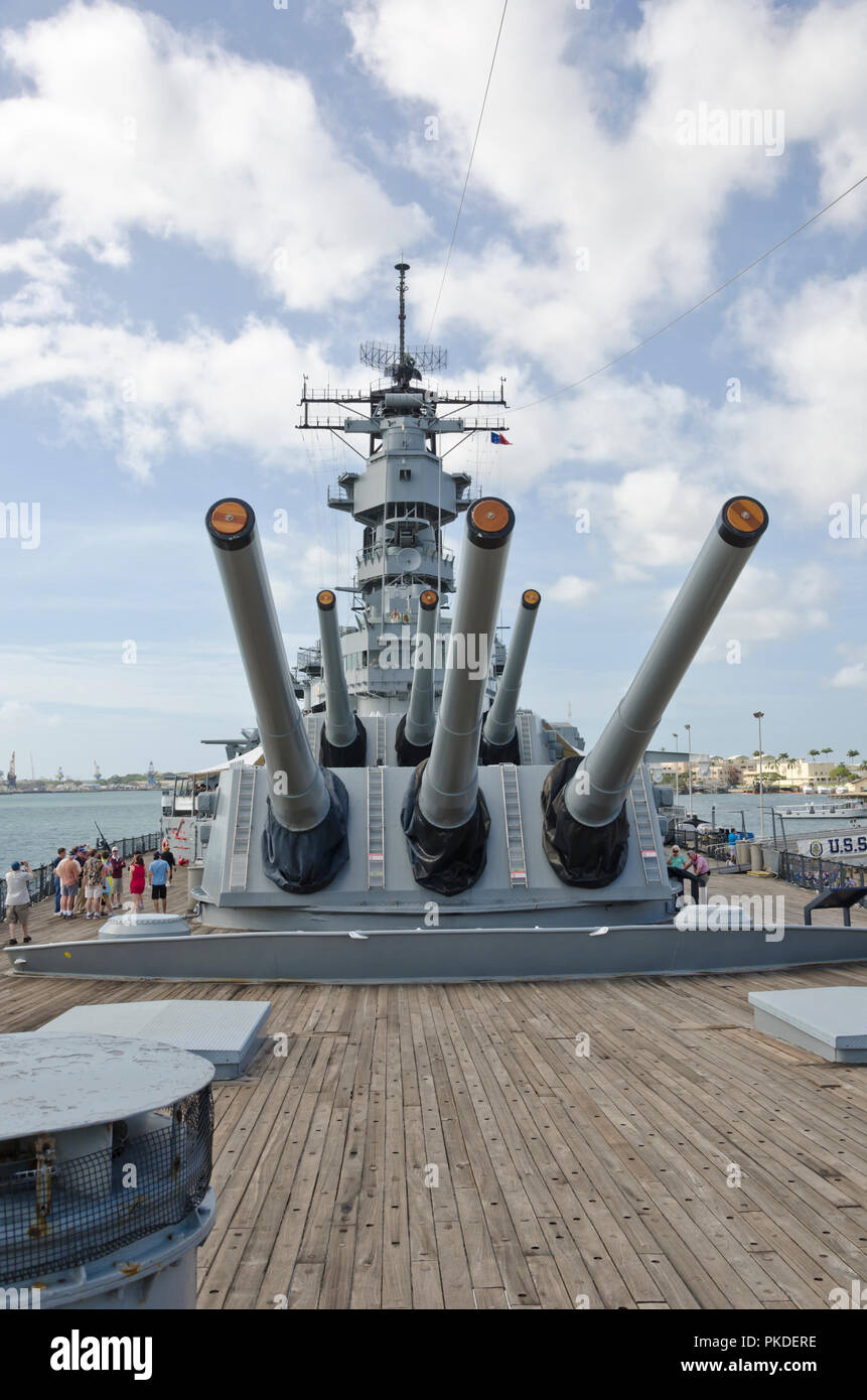 Tourists walk past gun turrets on USS Missouri (the ship on which the hostilities with Japan in WWII were officially ended) in Pearl Harbor, Hawaii. Stock Photo