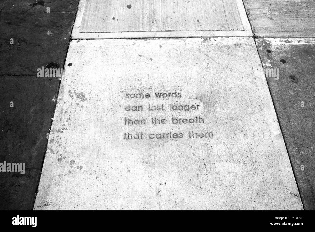 New concrete blocks in Appleton Wisconsin have inspiring words incised in the sidewalk - Stock Image