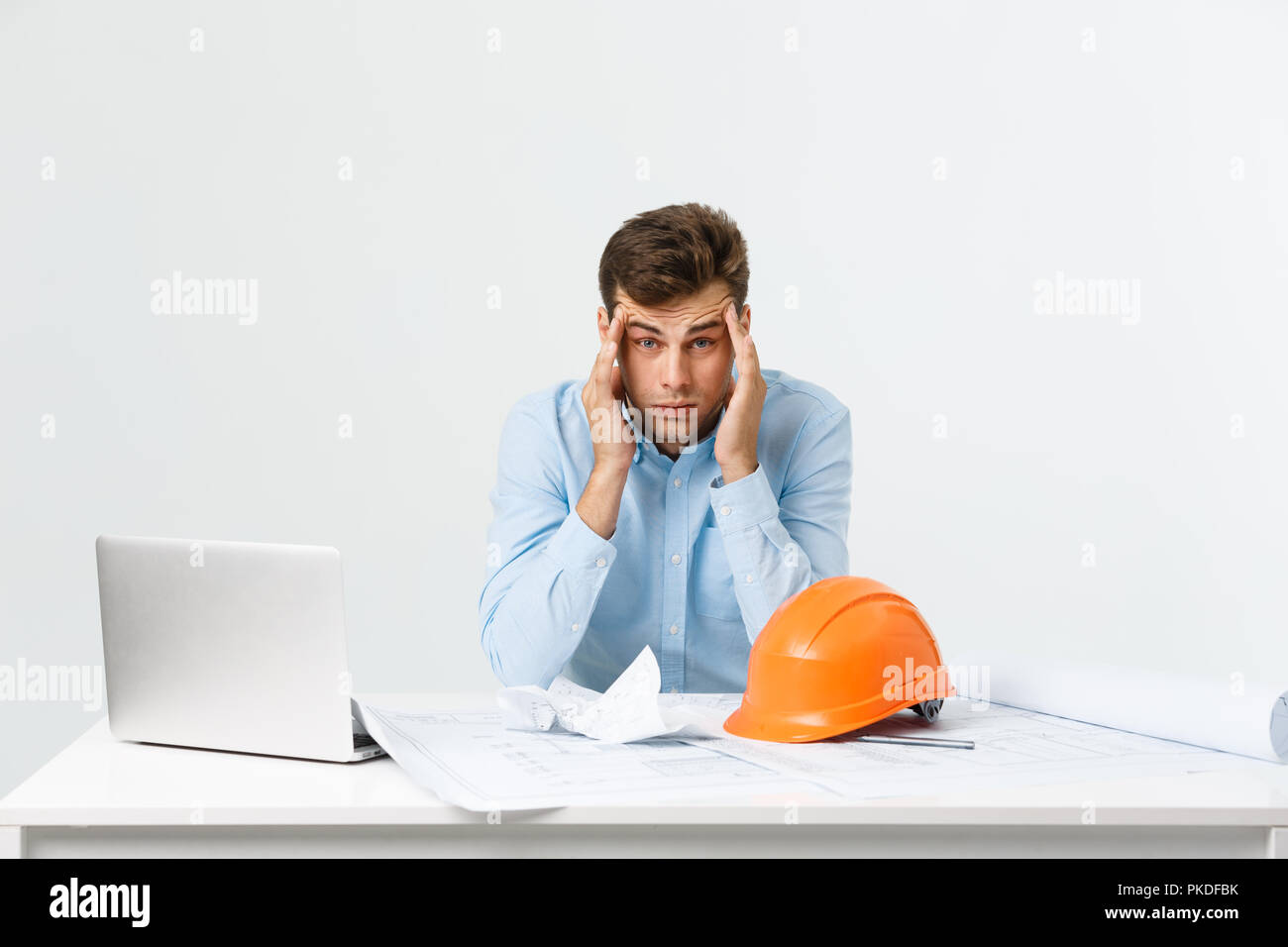 Portrait of engineer stress holding his head with hand sitting at the table and feel headache in the office on isolated background. Engineering concept. - Stock Image