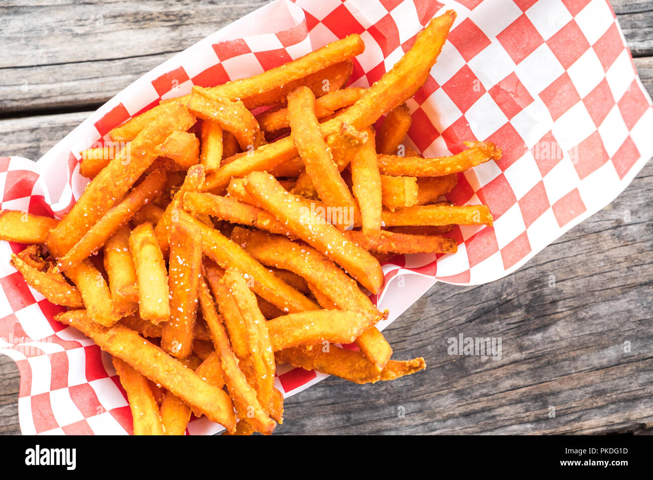 Paper basket of sweet potato fries with salt on rustic wooden table - Stock Image