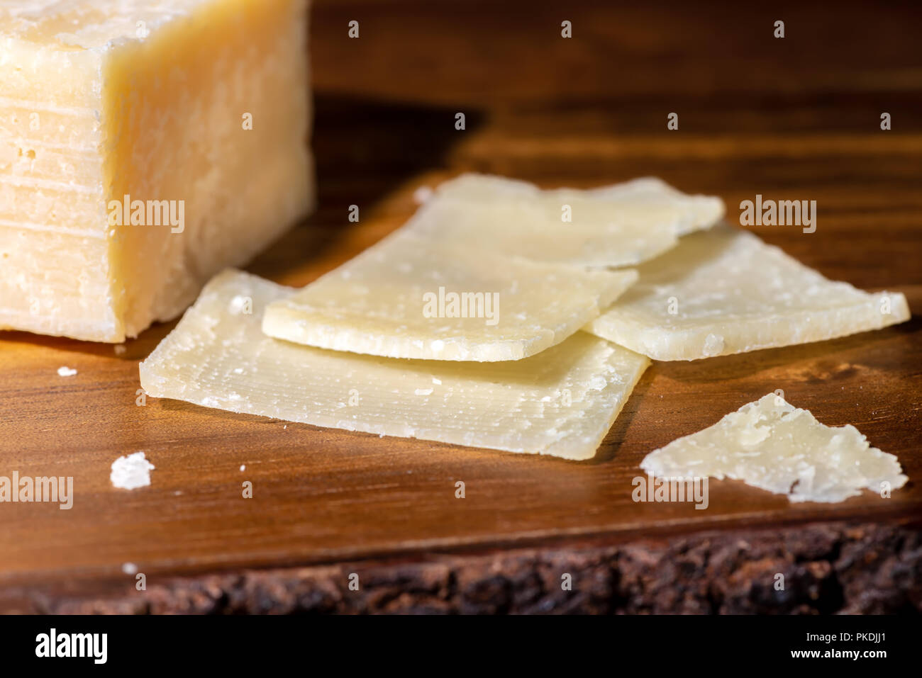 close up portion and slaced of fresh parmesan cheese on wooden background - Stock Image