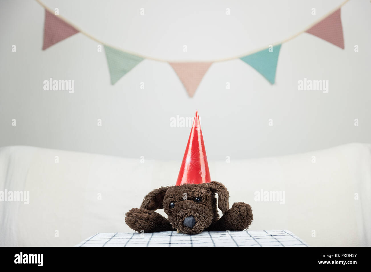 Children party concept with fluffy toy dog at the table. - Stock Image