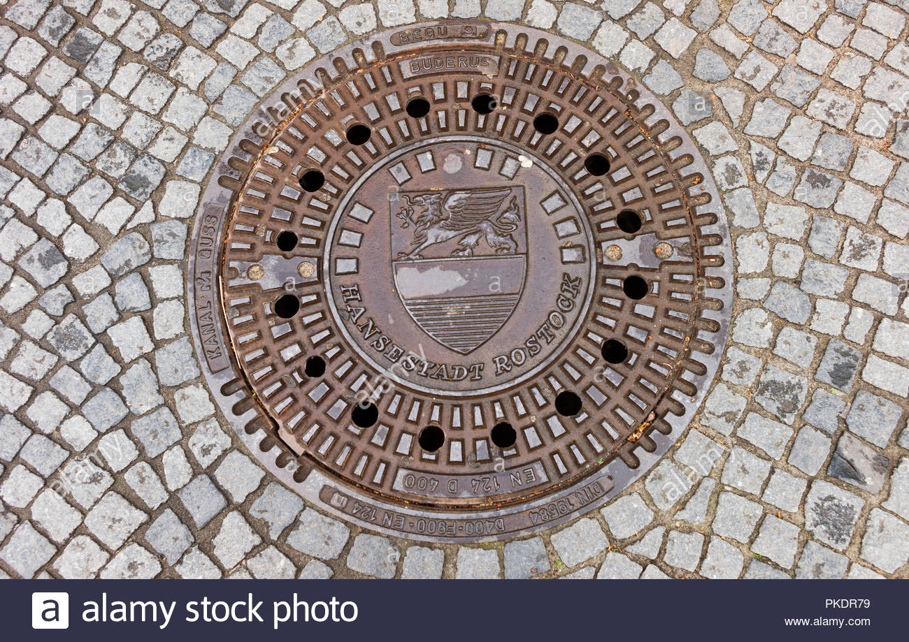 Cast iron drain cover set into a cobbled street in Rostok, Germany Stock Photo