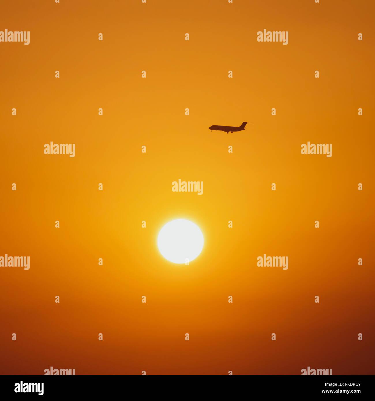 Passenger jet in sky at sunrise - Stock Image