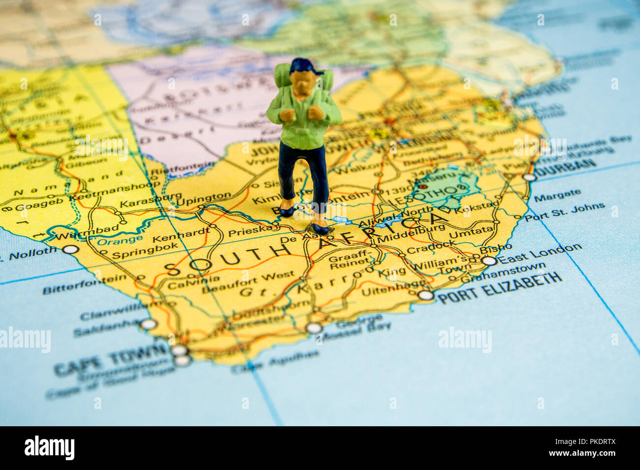 closeup of miniature figurine of young traveller standing on big