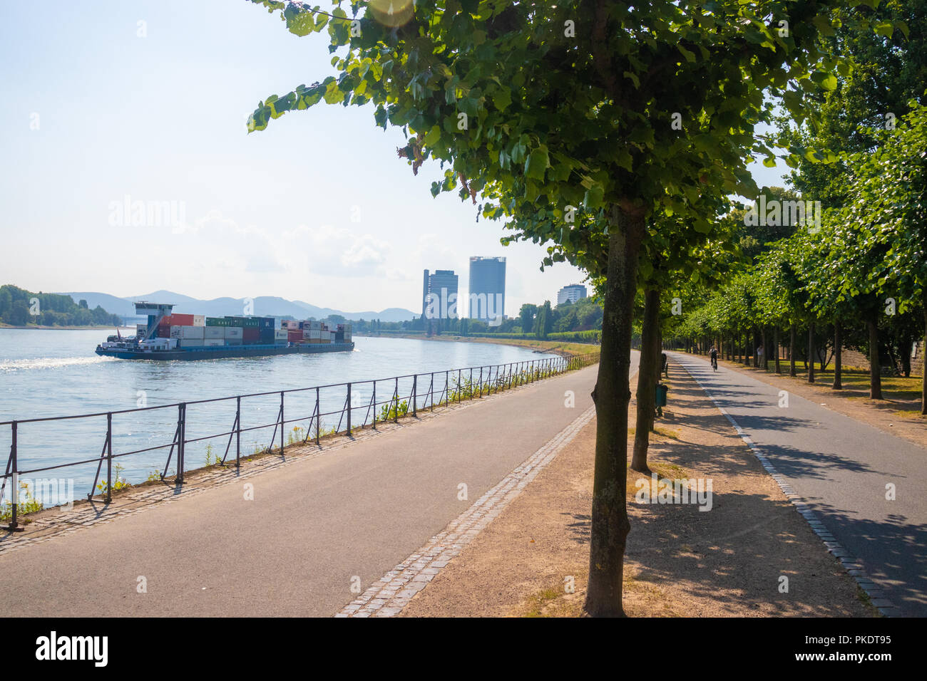 A view along the River Rhine Cycle and Footpaths with a cargo ship on the Rhine. Stock Photo