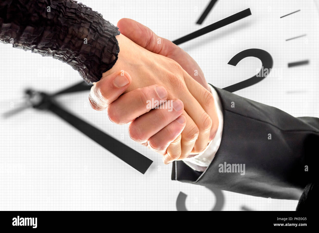 Man and woman business handshake with white clock in background. Stock Photo