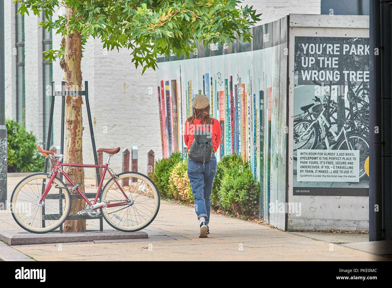 Young woman walks past a notice about parking a bicycle against a tree opposite the railway station at Cambridge, England. - Stock Image
