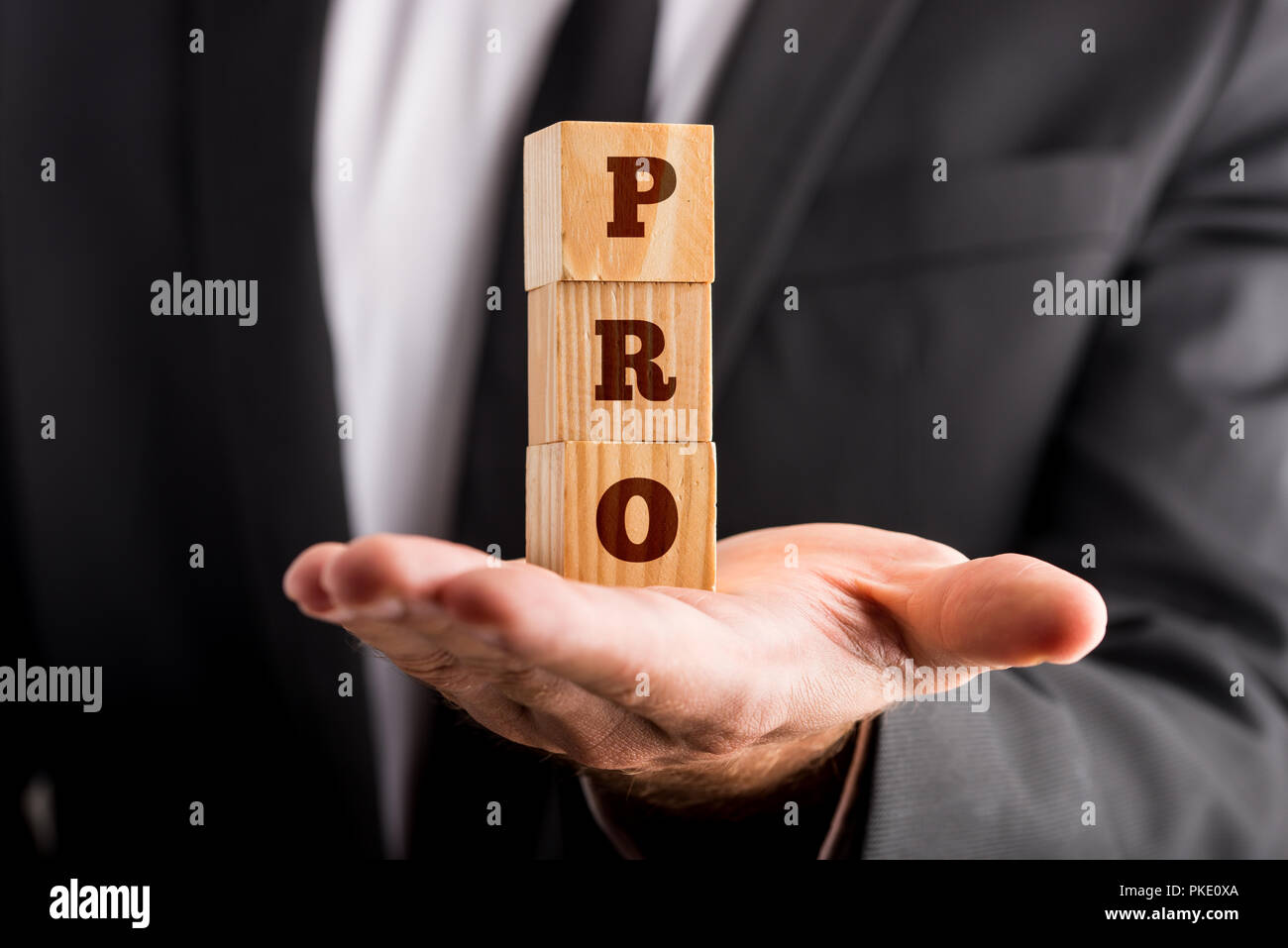 Businessman holding three wooden cubes stacked on the palm of his hand reading a PRO sign. Conceptual of professionalism and success. - Stock Image