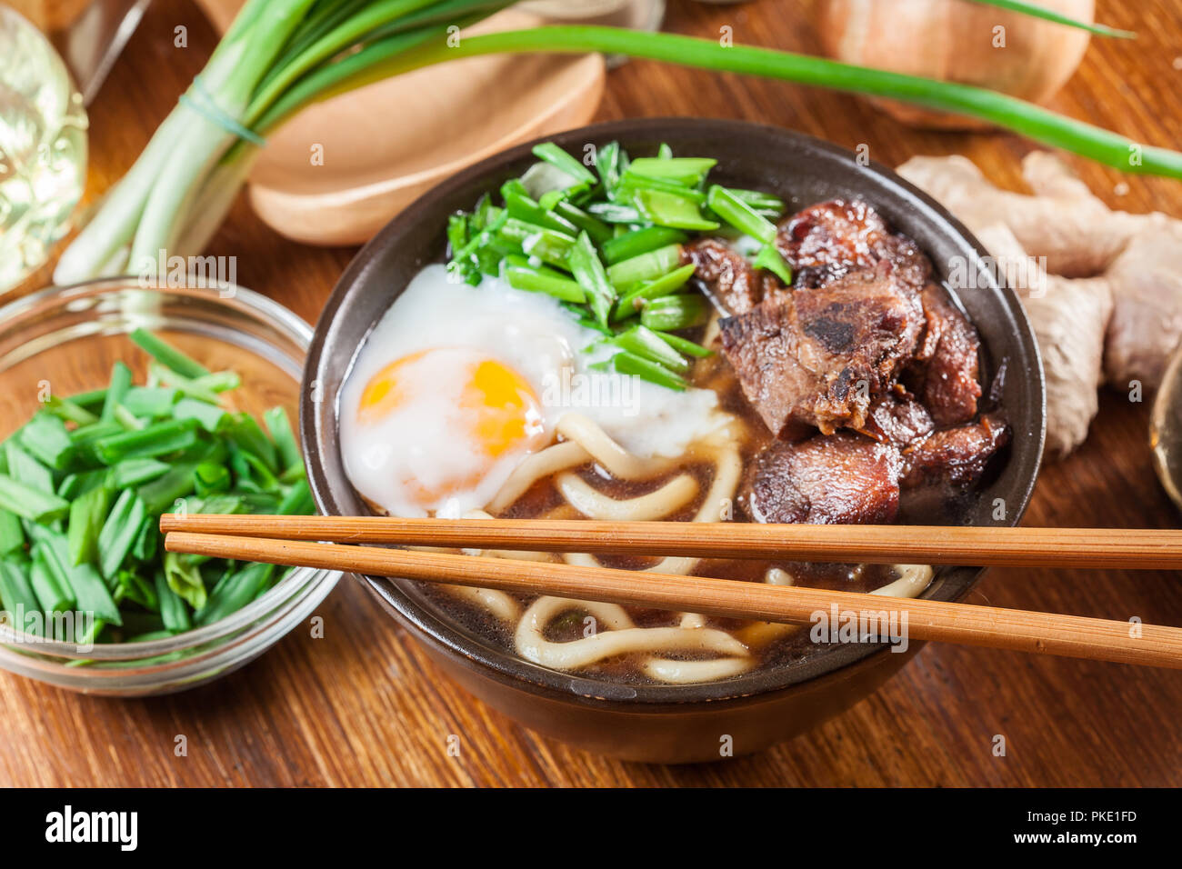 Japanese Udon noodles with beef, egg, green onion and soup in a brown bowl - Stock Image