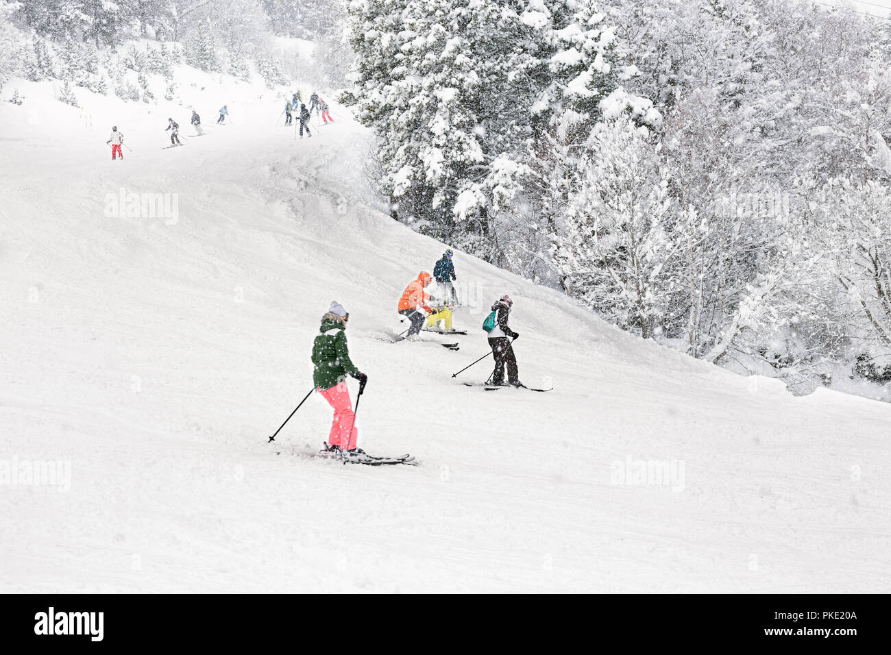 Downhill skiing during a heavy snowfall. Group of tourists, adults and children, on a resort slope in Andorra. - Stock Image