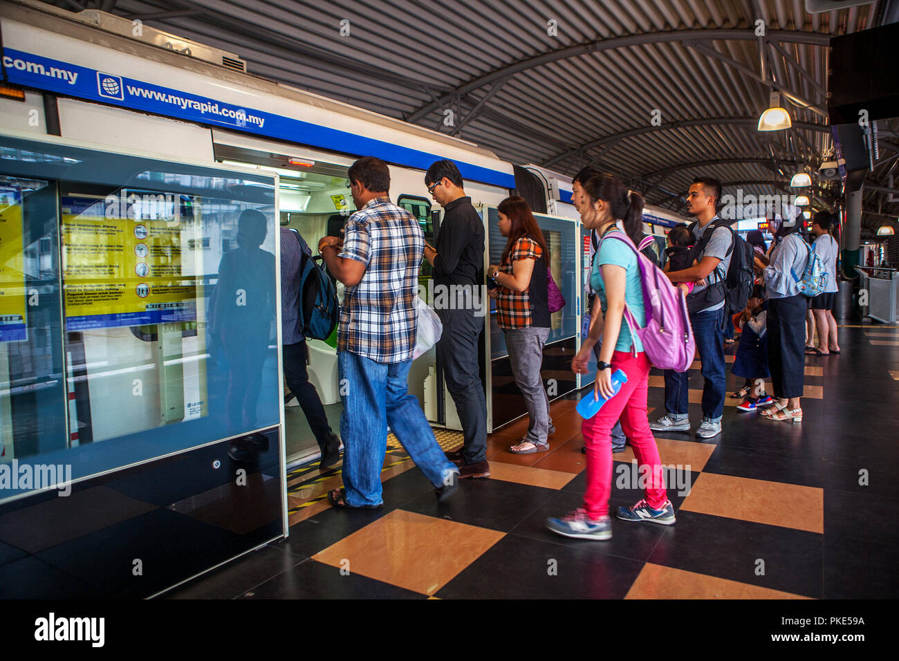 Passengers board one of the KL Rapid Transit monorail trains in Kuala Lumpur, Malaysia. - Stock Image