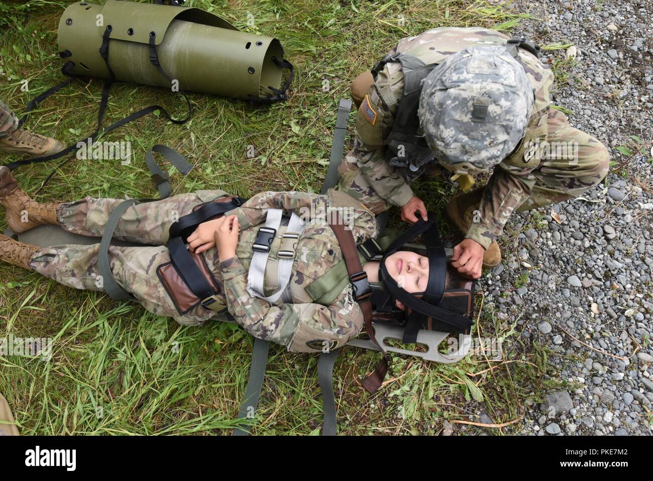 """U.S. Army Spc. Inook Cho from Charlie Company, 725th Brigade Support Battalion (Airborne), 4th Infantry Brigade Combat Team (Airborne), 25th Infantry Division, secures a simulated patient with a suspected spinal injury July 26, 2018 at Joint Base Elmendorf-Richardson, Alaska. The """"Cobra Medics"""" conducted a four day challenge to select two medics to be sent as competitors to the USARAK best medic competition. Stock Photo"""