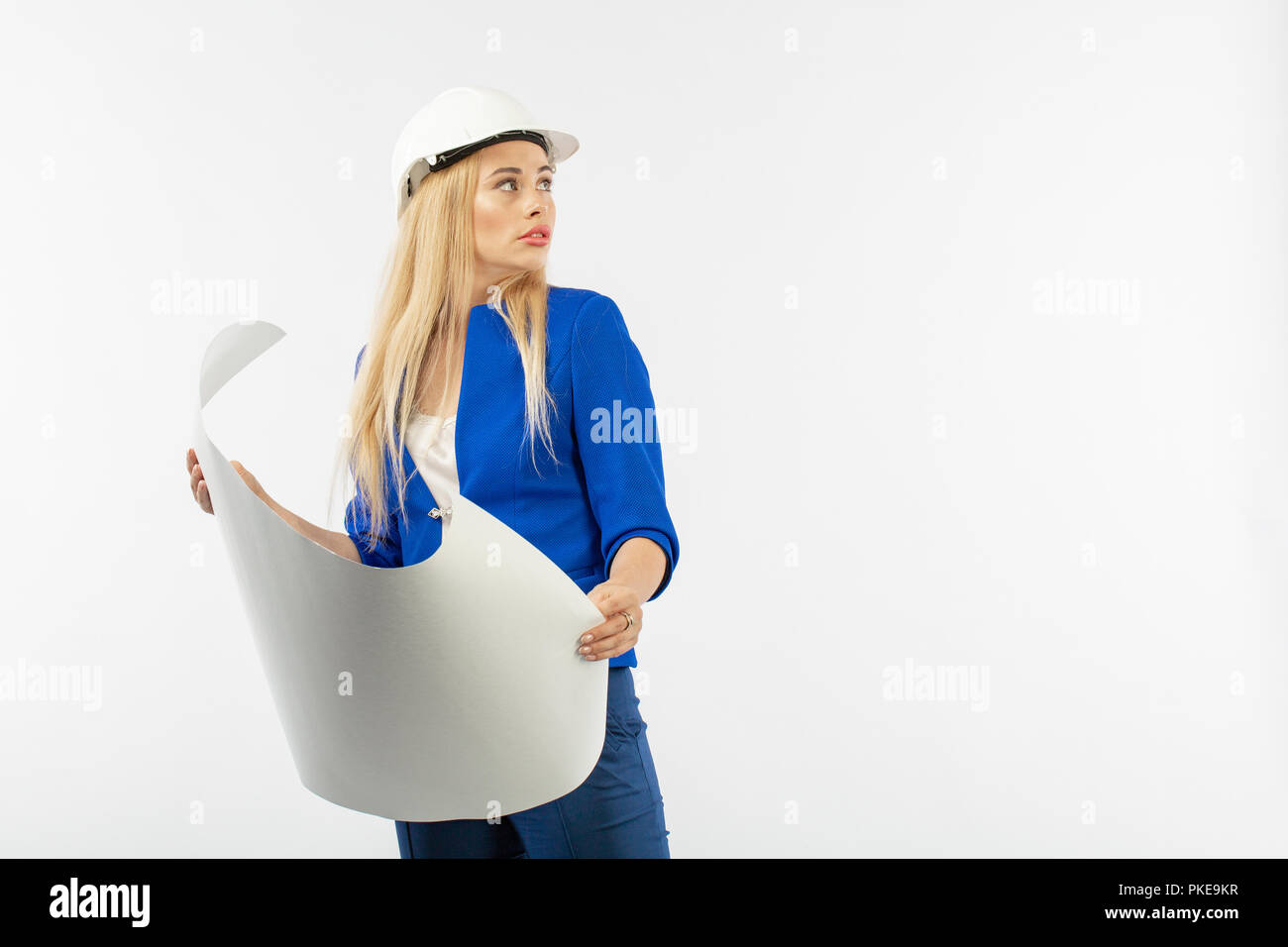 Employee woman in suit standing in helmet with paper documents on white background. architect considers drawings Stock Photo