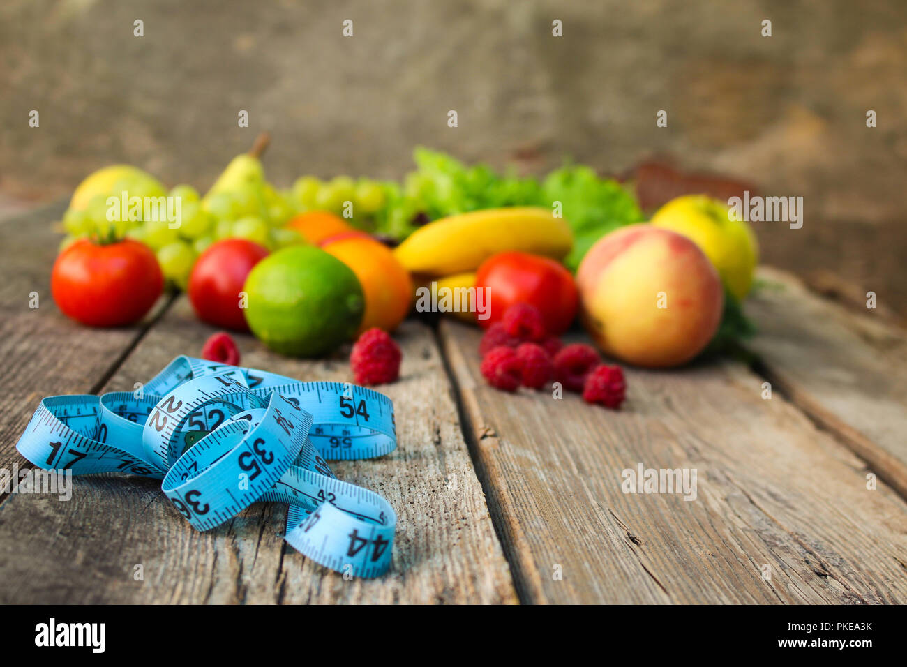 Fruits, vegetables, measure tape on wooden background. - Stock Image