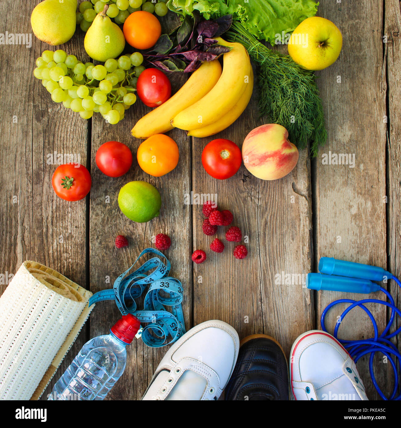 Fruits, vegetables and sports goods on wooden background. - Stock Image