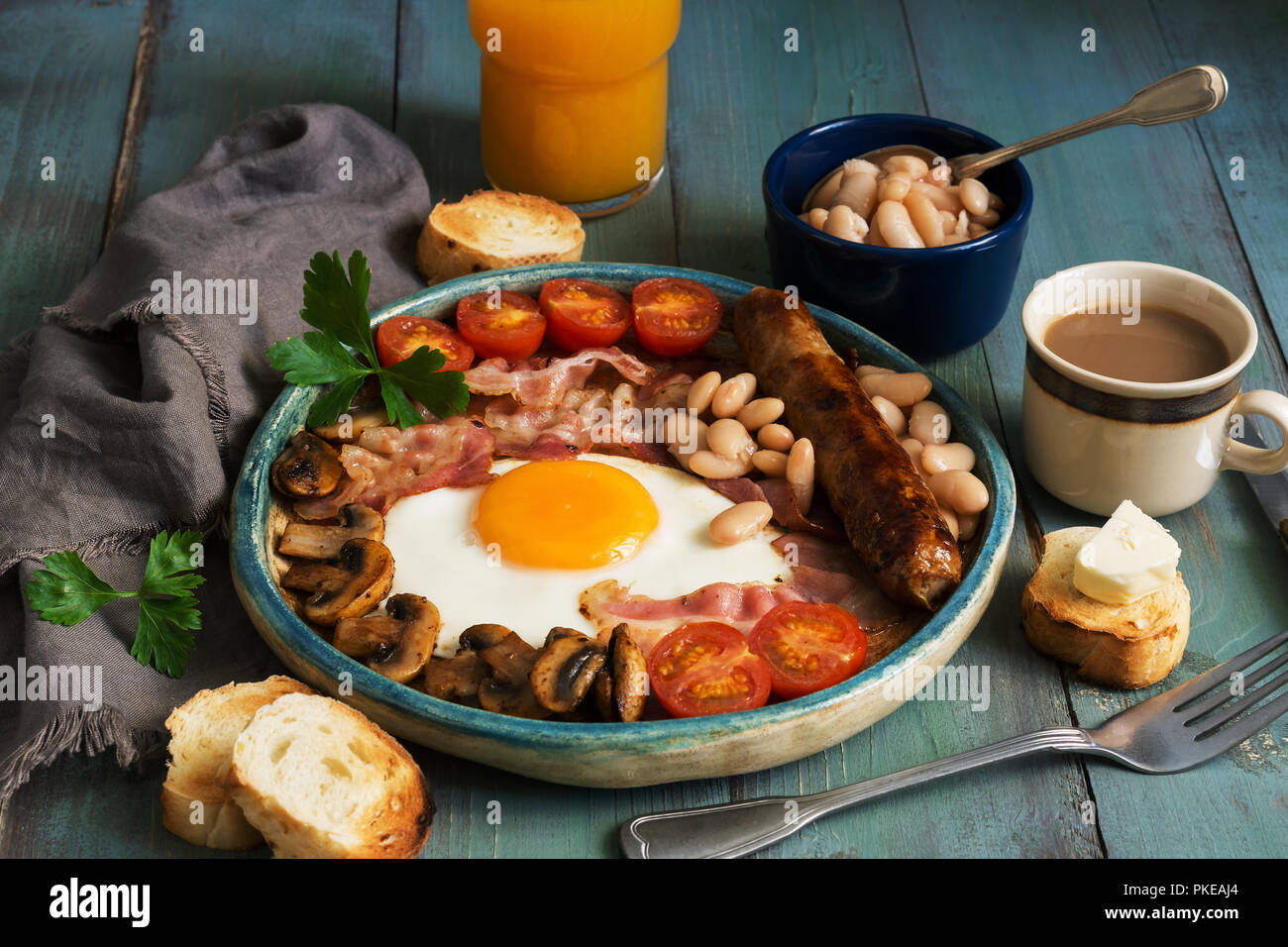 A traditional full English breakfast with fried egg, sausage, mushrooms, beans, bacon and tomatoes on a rustic wooden green table - Stock Image