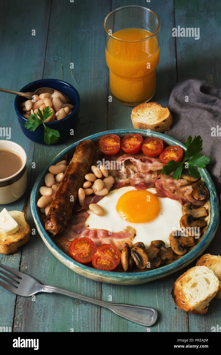 Full English breakfast with scrambled eggs, sausage, mushrooms, beans and bacon on a wooden rustic green table - Stock Image