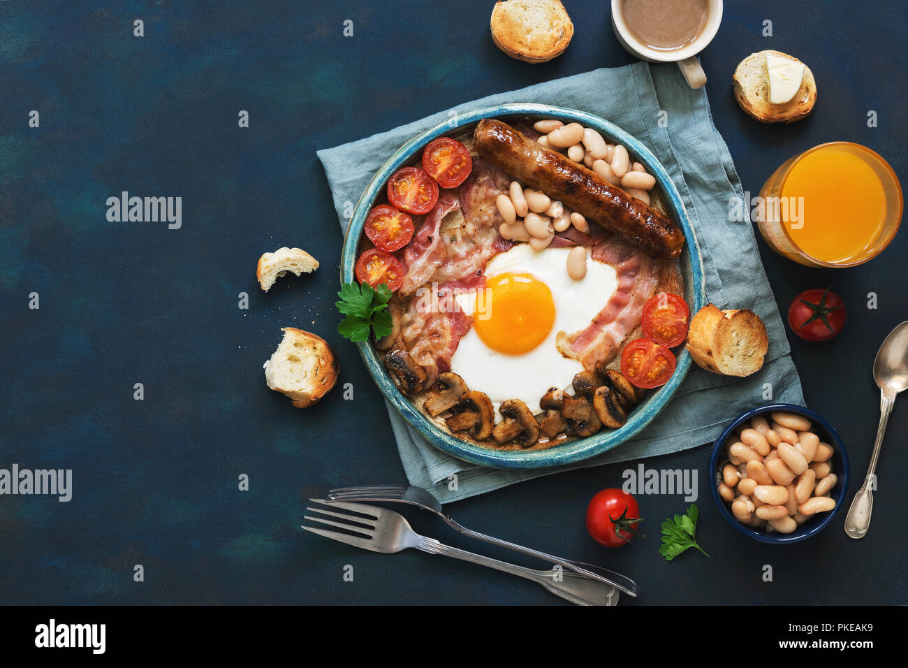 Traditional English breakfast on a blue background. Fried egg with sausage, mushrooms, beans, tomatoes and bacon. Top view, copy space - Stock Image