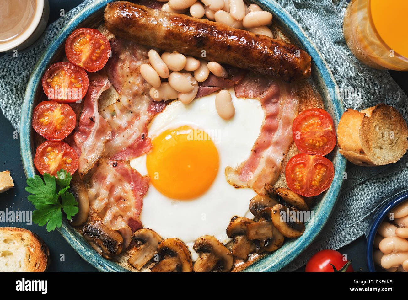 Traditional English breakfast close-up on a blue background, top view. Fried egg with sausage, mushrooms, beans, tomatoes and bacon. - Stock Image