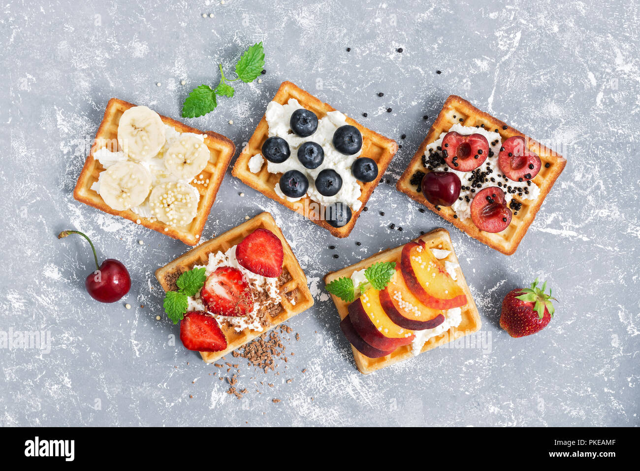 A view from above of a wafer with a cream of fruit and berries on a gray background. Traditional Belgian waffles - Stock Image