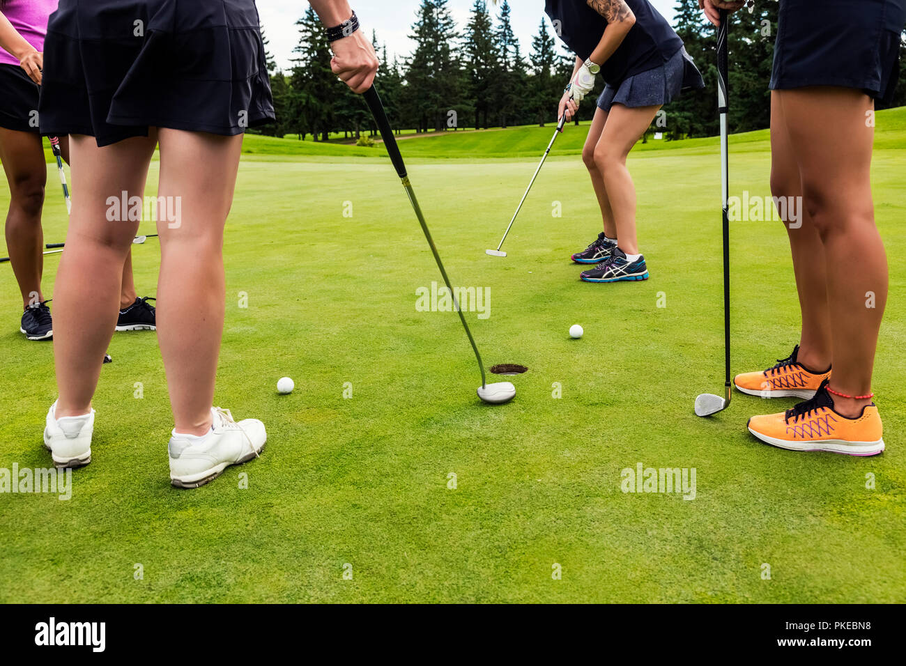 A foursome of female golfers on a putting green taking turns putting using the best ball in a Texas Scramble during a tournament Stock Photo