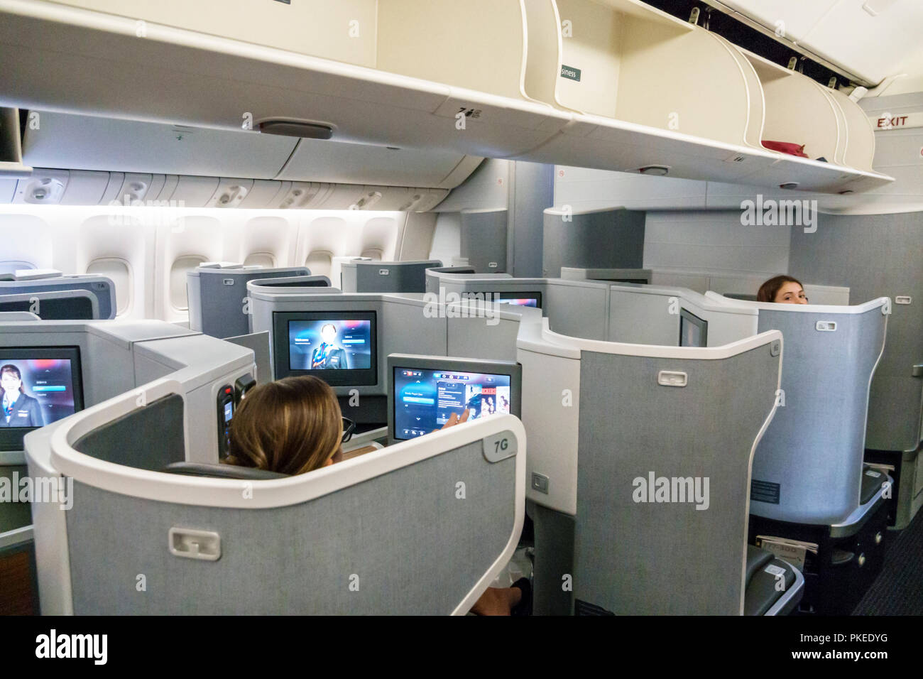 Miami Florida International Airport MIA American onboard Airlines flight 56 business class seat seating cabin inside seatback screens open overhead lu - Stock Image