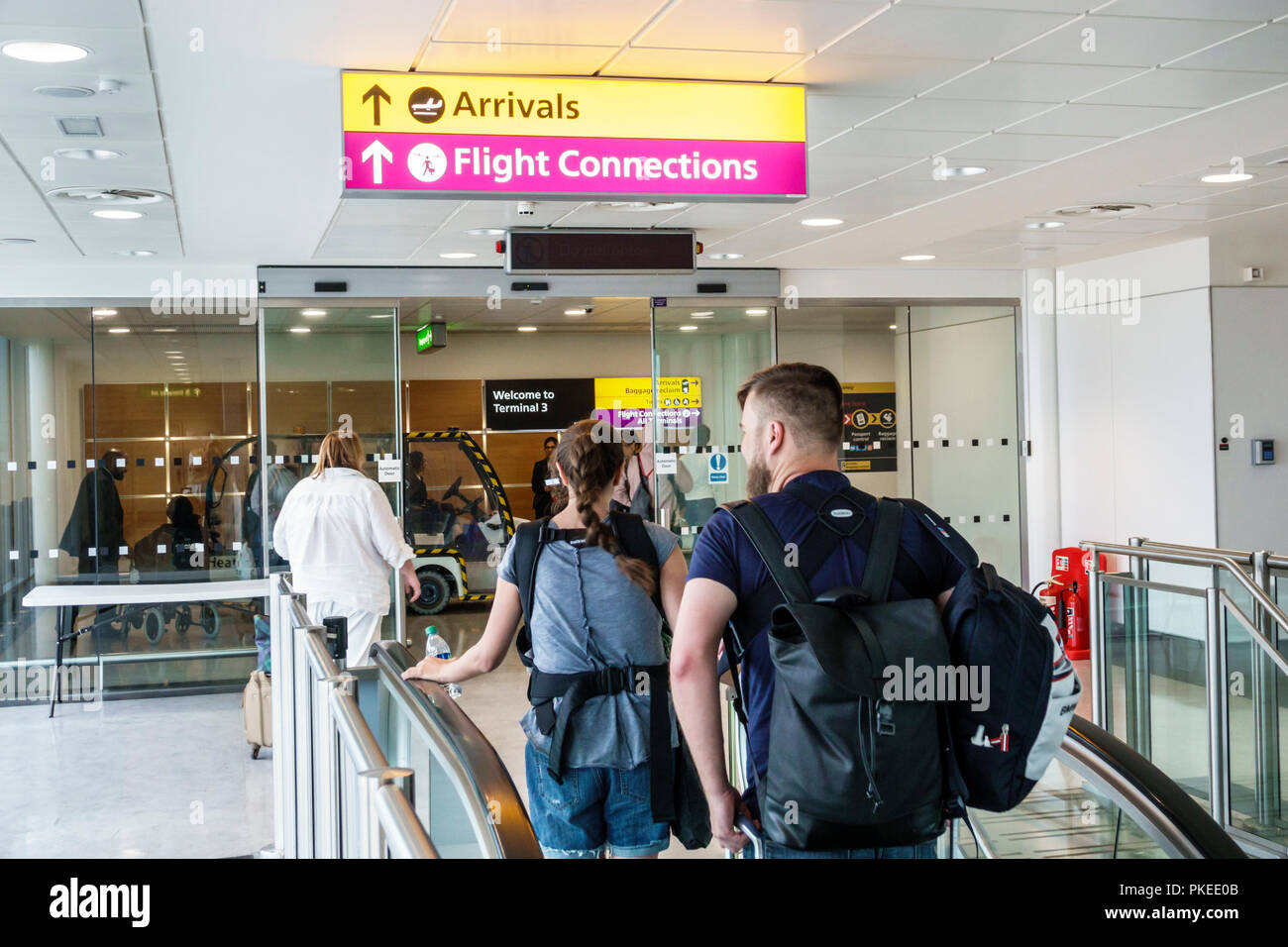 London England Great Britain United Kingdom Heathrow Airport LHR flight arrivals connections man woman passenger - Stock Image