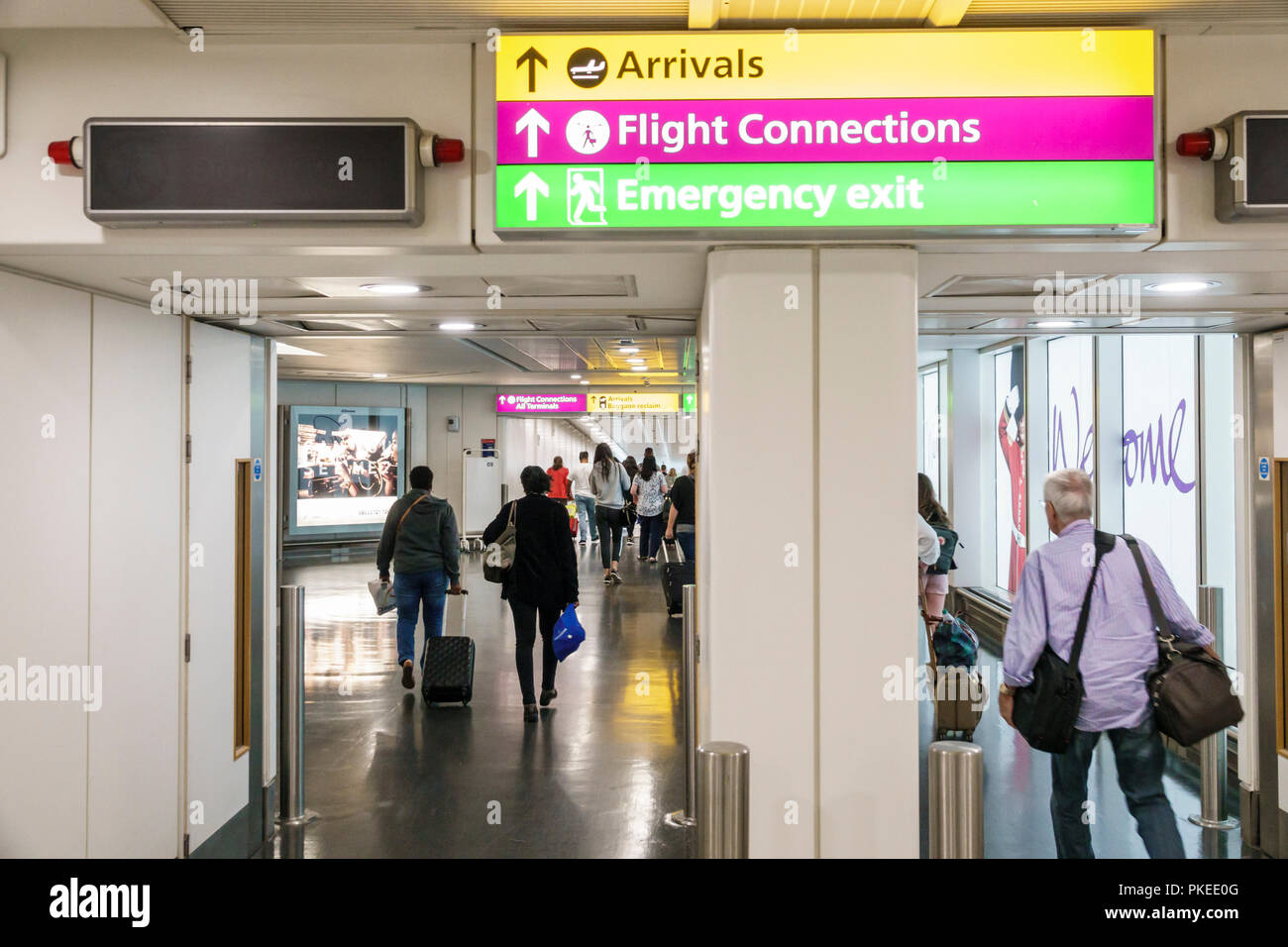 London England Great Britain United Kingdom Heathrow Airport LHR directions sign flight arrivals connections emergency exit man woman passenger - Stock Image
