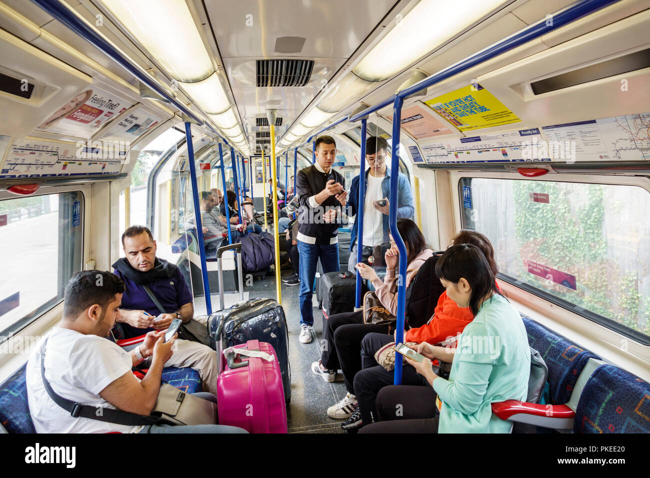 London England Great Britain United Kingdom Underground Tube public transportation system rapid transit Picadilly Circus Line train inside Asian man w - Stock Image