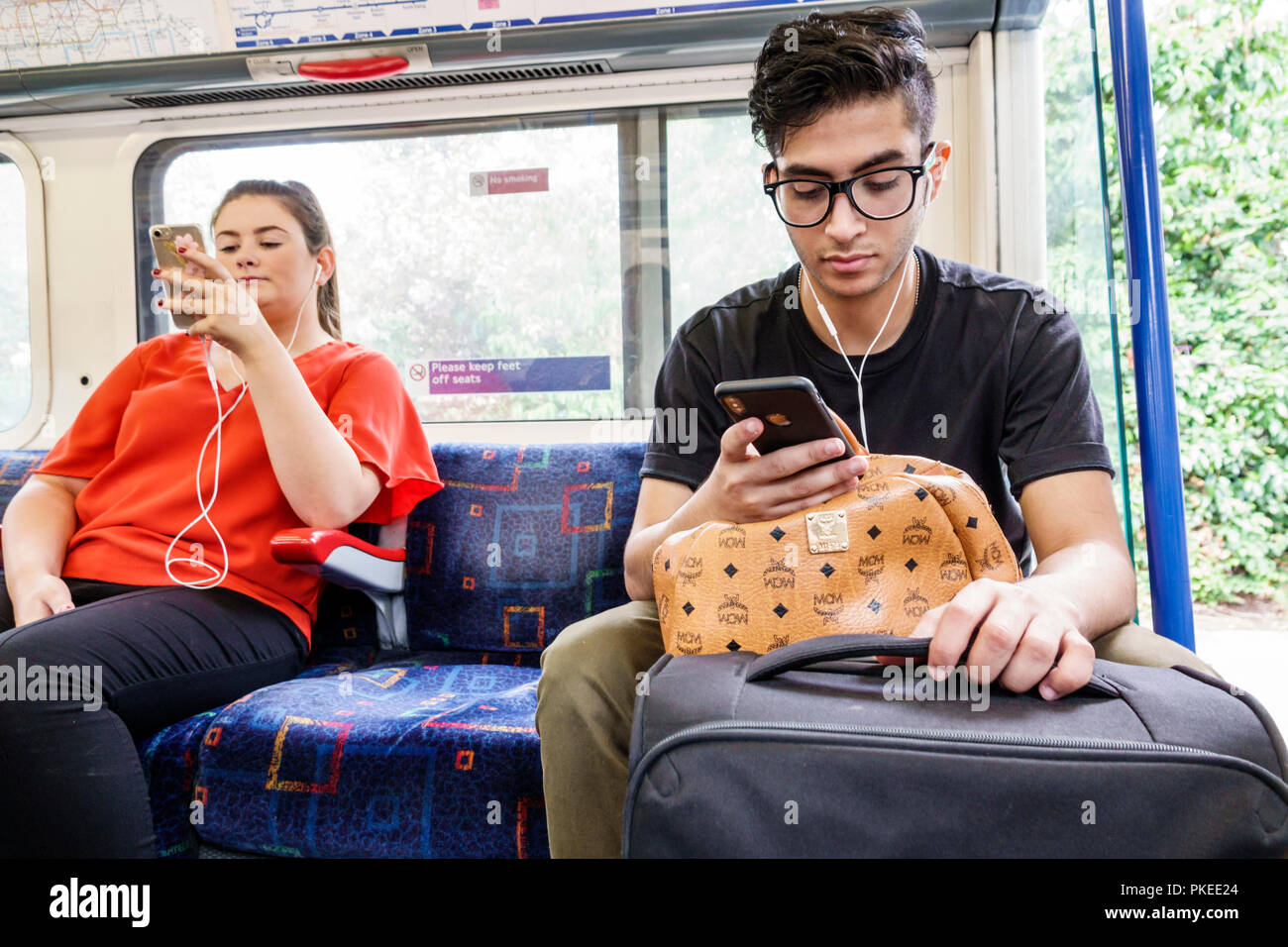 London England Great Britain United Kingdom Underground Tube public transportation system rapid transit Picadilly Circus Line train inside man woman s - Stock Image
