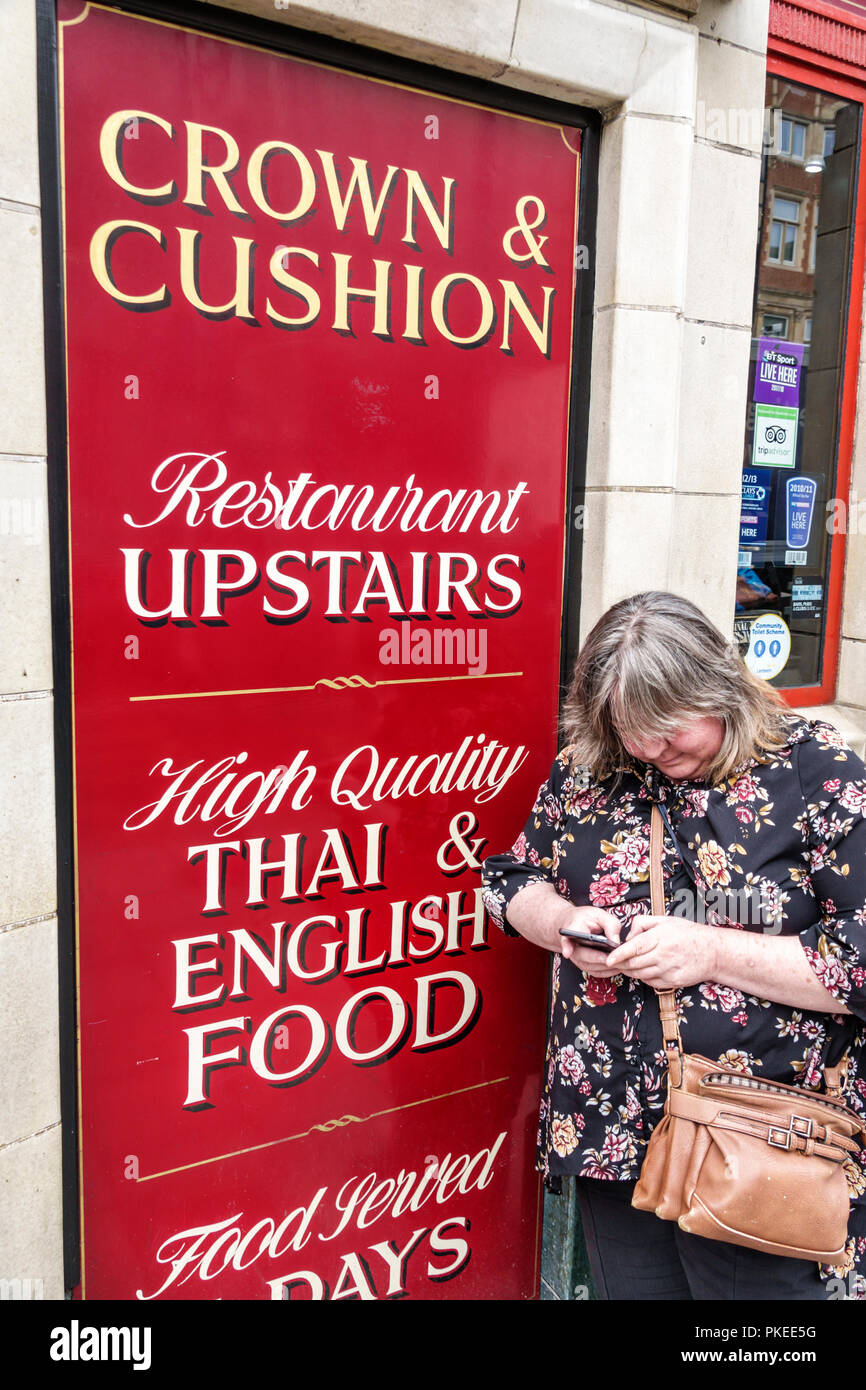 London England Great Britain United Kingdom South Bank Lambeth Crown & Cushion restaurant sign exterior woman passerby mature texting smartphone - Stock Image
