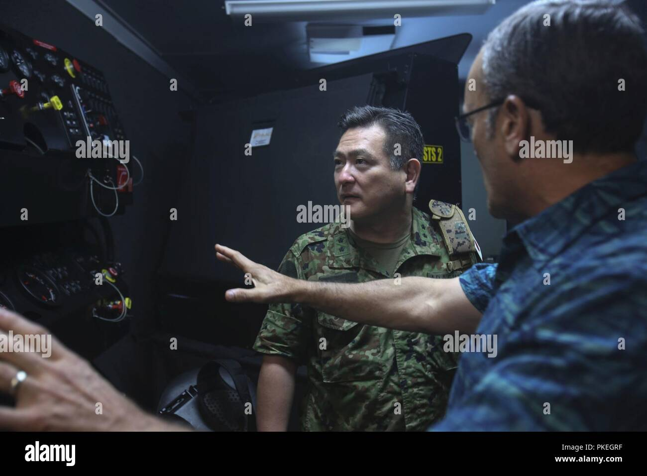 Major Gen. Yoshiki Adachi, defense and military attaché, Embassy of Japan, is briefed on the schematics of a controlled driving simulator on Camp Lejeune, N.C., Aug. 3, 2018. Adachi is visiting the Marines and Sailors of II Marine Expeditionary Force to continue to build relationships and understand II MEF's mission and activities in the western hemisphere in regards to its amphibious capabilities and operations. - Stock Image
