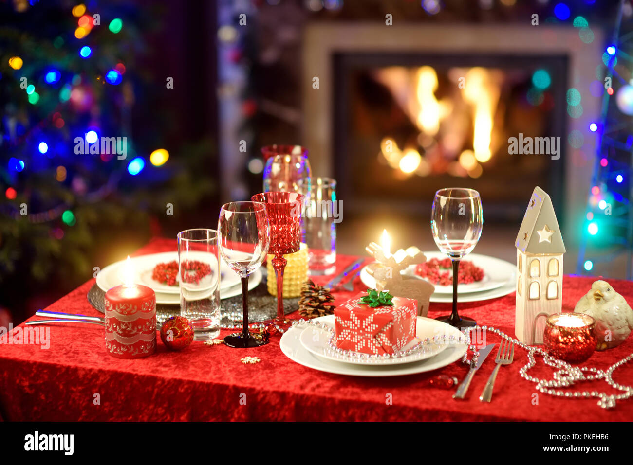 Beautiful table setting for Christmas party or New Year celebration at home. Cozy room with a fireplace and Christmas tree in a background. Xmas time  Stock Photo