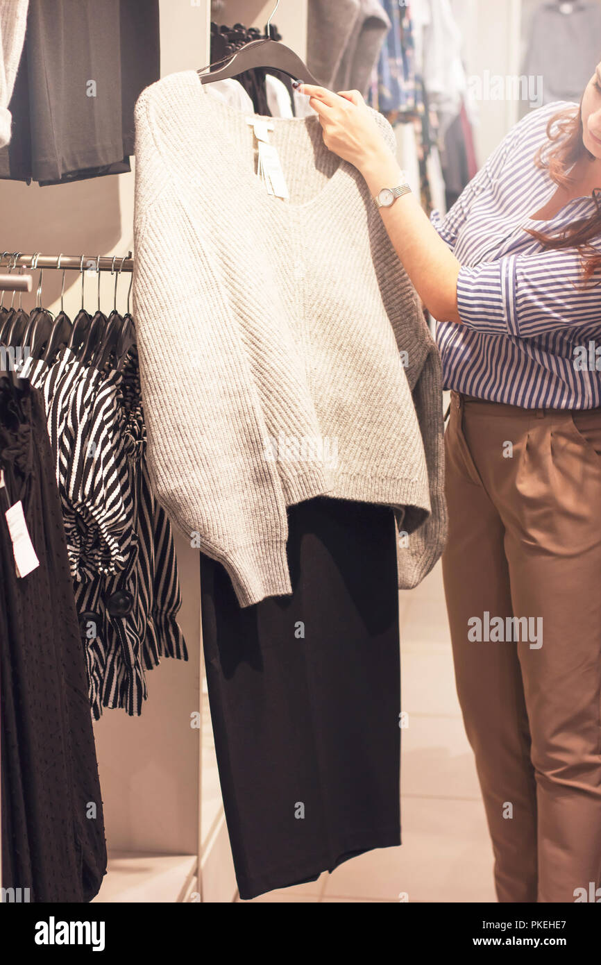 Young woman stylist shopper chooses clothes in the store Stock Photo