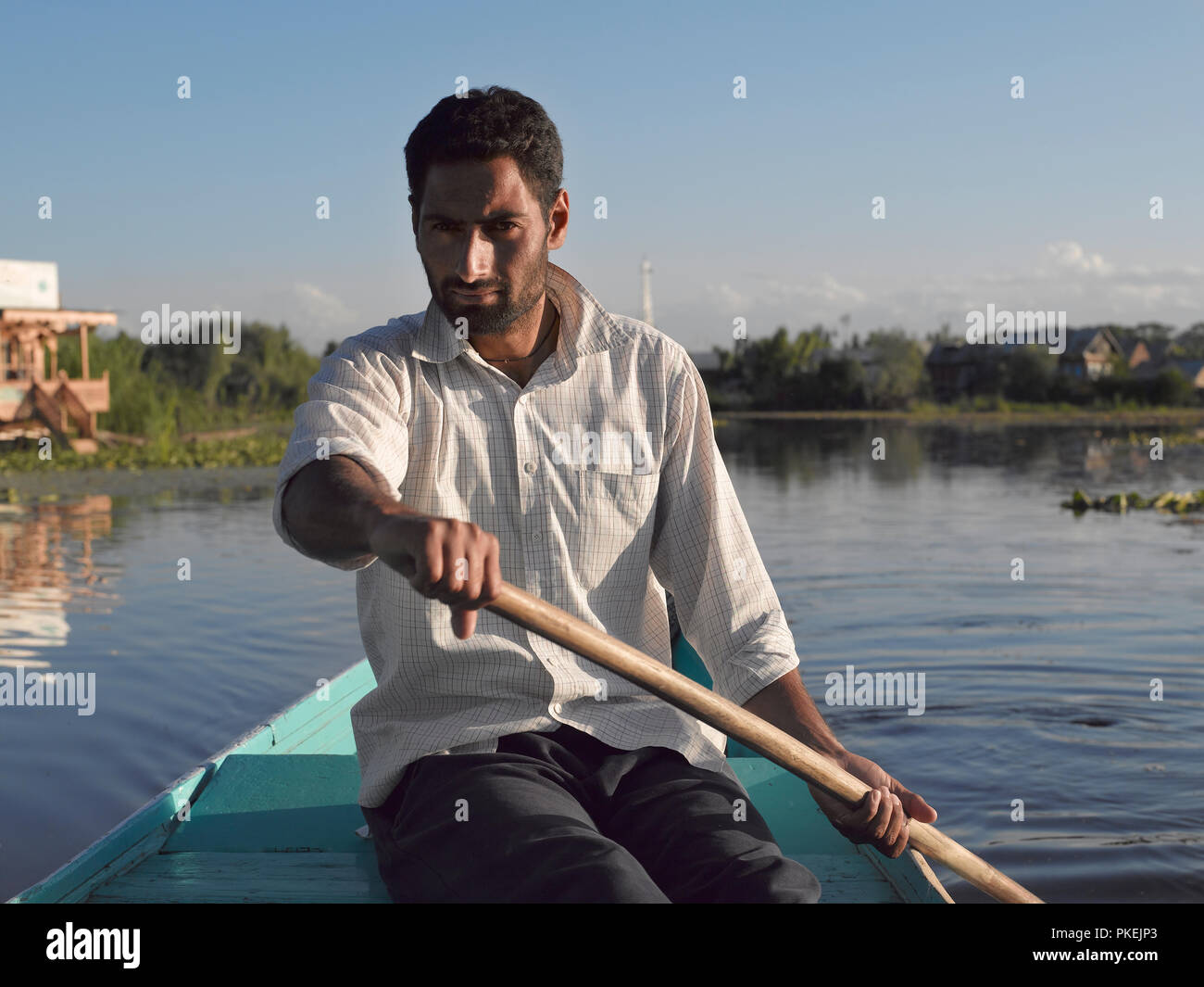A Kashimiri man rows a boat used for tourist rides on Dal Lake, SRINAGAR, KASHMIR, INDIA, ASIA Stock Photo