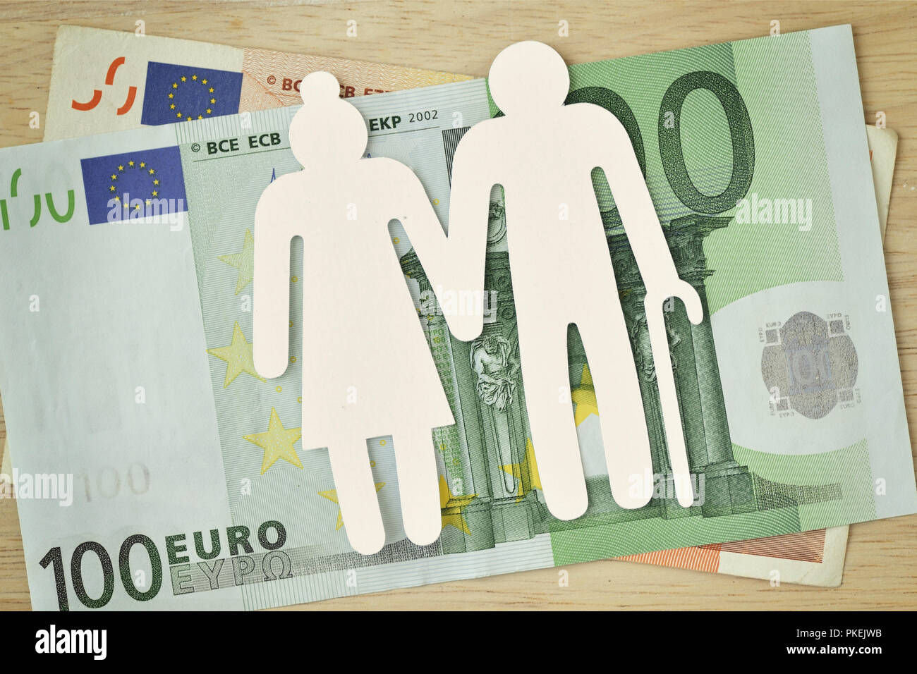 Paper elderly couple cut-out on euro banknotes - Pension concept Stock Photo