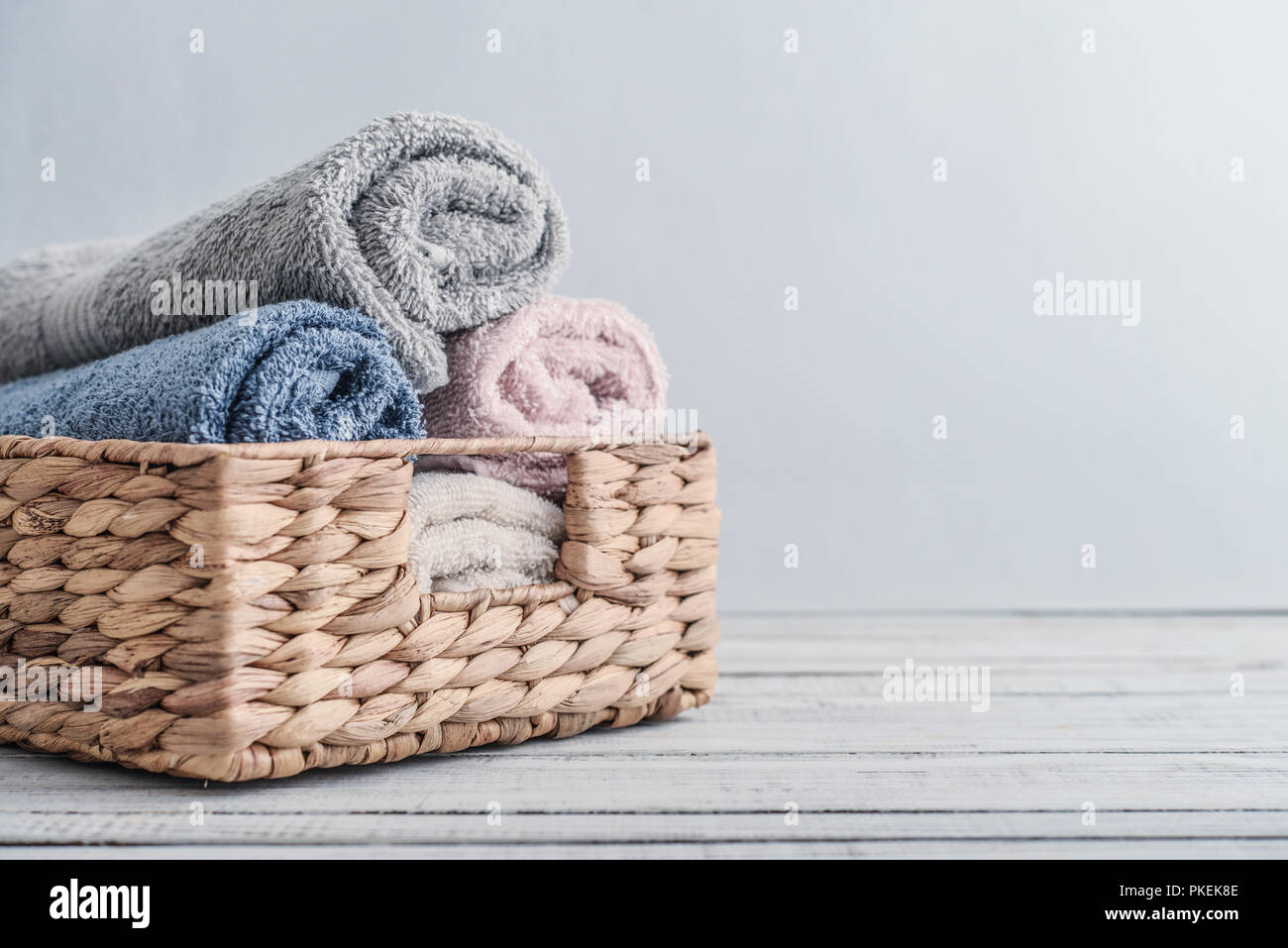 Bath towels of different colors in wicker basket on light background - Stock Image