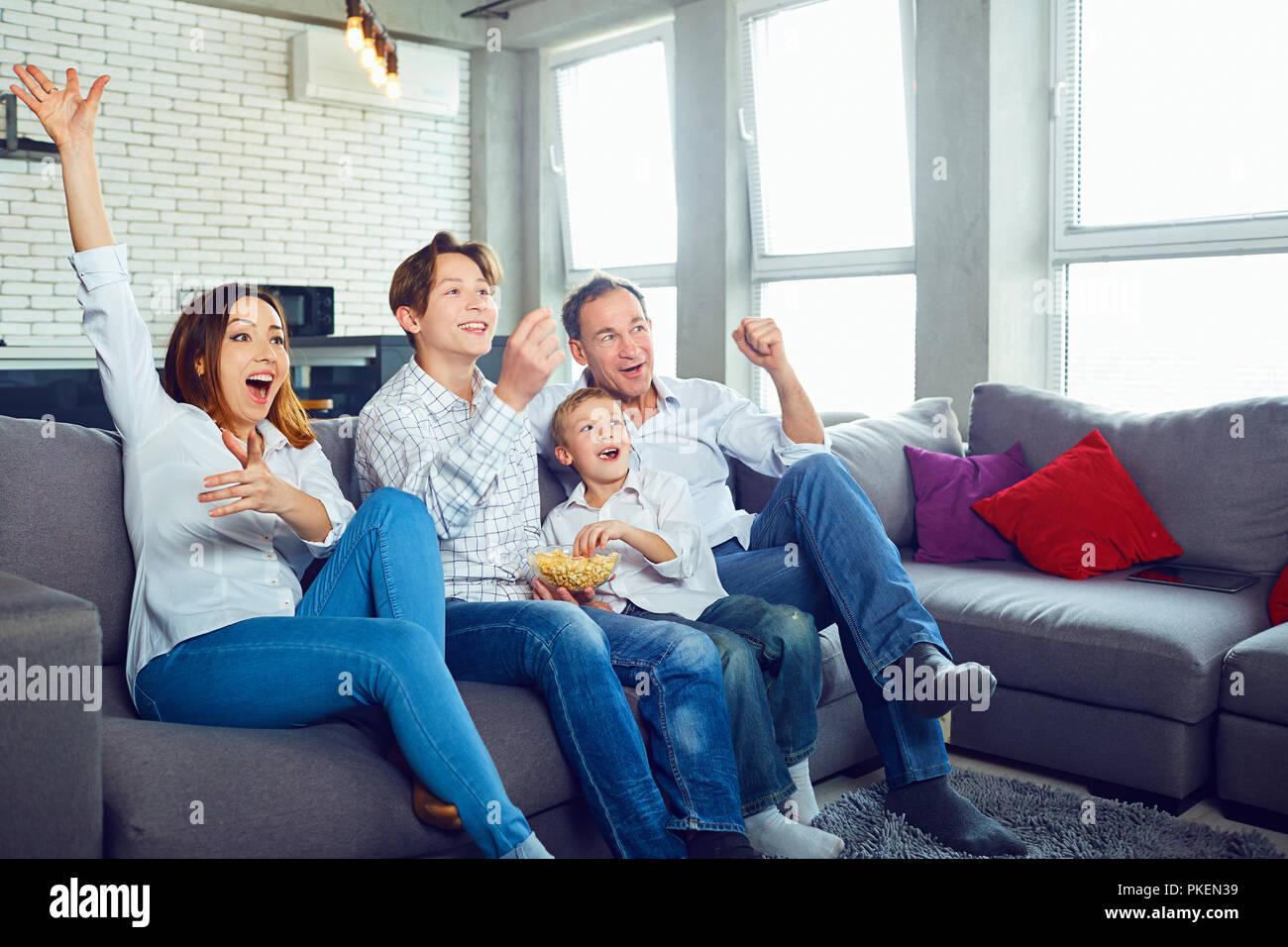 Happy family having fun watching TV sitting. - Stock Image