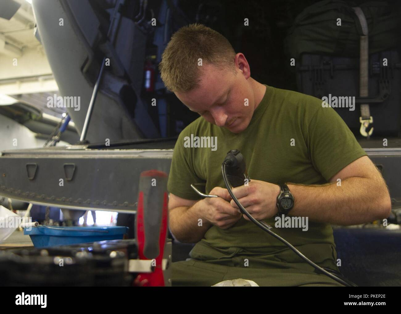 "PACIFIC OCEAN (July 30, 2018) – Marine Corps Cpl. Daniel Holyoke, assigned to the ""Sea Elks"" of Marine Medium Tiltrotor Squadron (VMM) 166 (REIN), etches tools in the hangar bay of Wasp-class amphibious assault ship USS Essex (LHD 2) during a regularly scheduled deployment of the Essex Amphibious Ready Group (ARG) and 13th Expeditionary Unit (MEU). The Essex ARG/13th MEU is a capable and lethal Navy-Marine Corps team deployed to the 7th fleet area of operations to support regional stability, reassure partners and allies and maintain a presence postured to respond to any crisis ranging from hum - Stock Image"