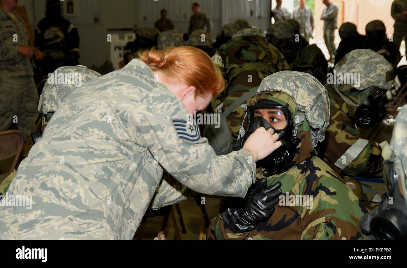 ALPENA, Mich.-- An instructor with the 127th Civil Engineering Squadron assists Tech Sgt. Chanel Daniels, 127th Force Support Squadron, in adjusting her gas mask during Battle Lab training at the Alpena Combat Readiness Training Center on July 29, 2018. During the training, Airmen of the 127th Wing, like Daniels, practiced donning and removing different levels of chemical protection equipment during an operational readiness assessment exercise. Stock Photo
