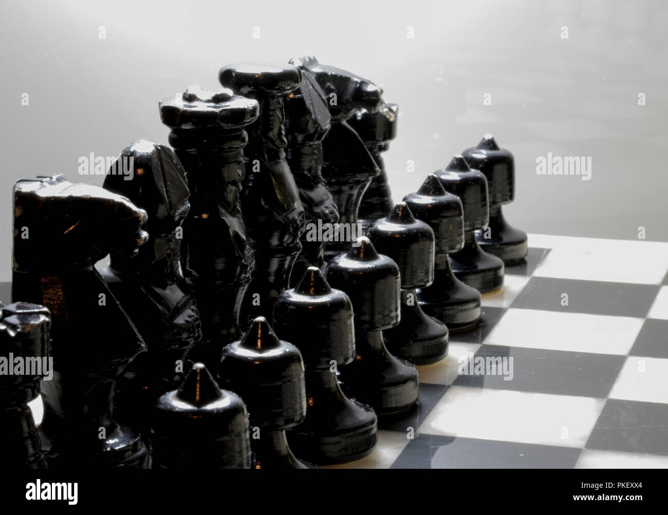 Black chess pieces lined up on a marble chess board. - Stock Image
