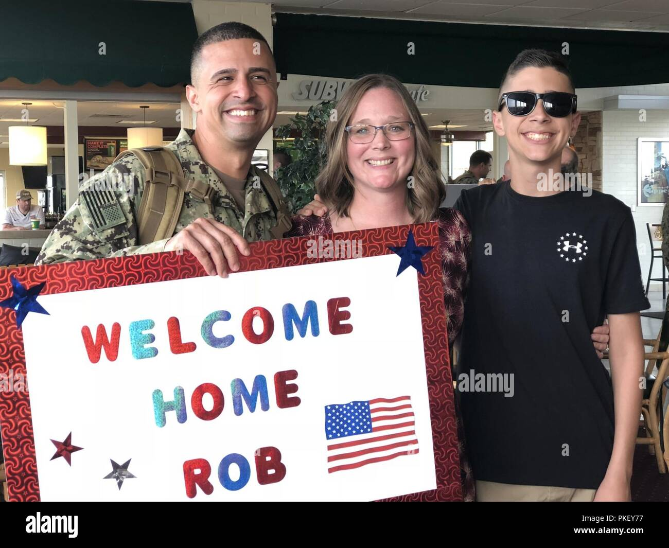 Coast Guardsmen, who is assigned to Port Security Unit 309, hugs his family upon arrival on July 29, 2018. Port Security Unit 309 returned to Port Clinton, OH after being deployed to Guantanamo Bay, Cuba, for nine months in support of Operation Freedom's Sentinel. PSUs serve as anti-terrorism force protection expeditionary units with boat crews and shore-side security teams capable of supporting port and waterway security anywhere the military operates. U.S. Coast Guard Stock Photo