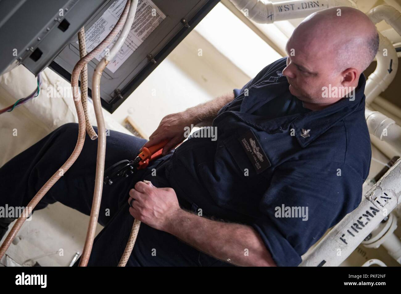 TALLINN, Estonia (Aug. 4, 2018) Electrician's Mate 2nd Class Matthew Holland repairs electrical equipment aboard the Arleigh Burke-class guided-missile destroyer USS Winston S. Churchill (DDG 81), Aug. 4, 2018. Winston S. Churchill, homeported at Naval Station Norfolk, is conducting naval operations in the U.S. 6th Fleet area of operations in support of U.S. national security interests in Europe and Africa. Stock Photo