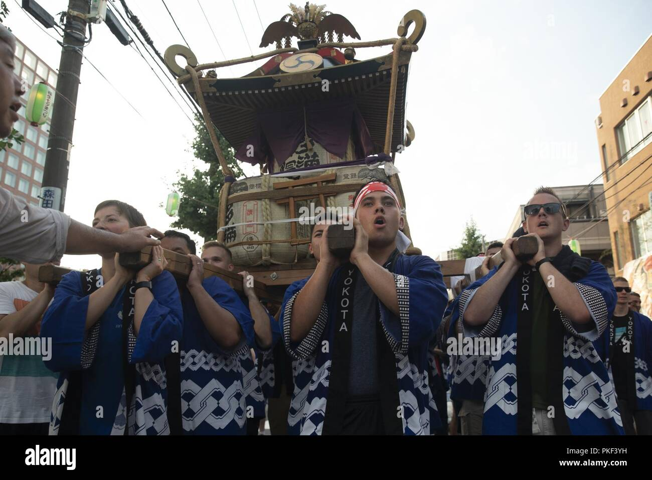 Members from Yokota Air Base carry the 374th Airlift Wing's official mikoshi during the 68th Annual Fussa Tanabata Festival at Fussa City, Japan, Aug. 3, 2018. More than 70 volunteers from Yokota carried the mikoshi during this year's festival. Yokota Airmen have attended the festival since 1958 and have actively participated in carrying a mikoshi since 1975. - Stock Image