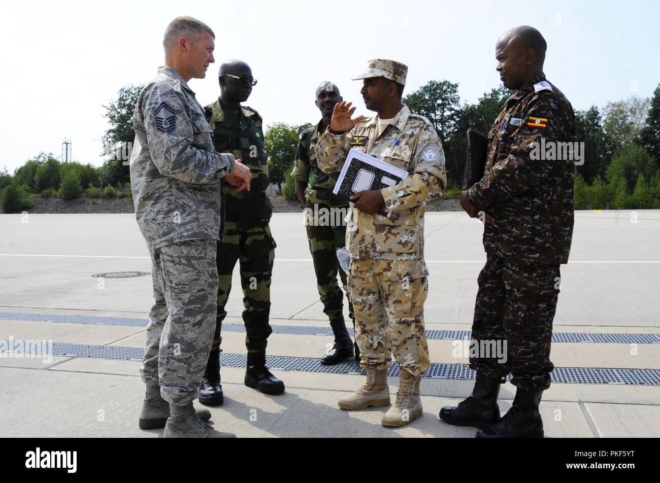 U.S. Air Force Senior Master Sgt. Ronald Robinette, Leaders Production Superintendent, assigned to 86th Air Maintenance Squadron, converses with participants of African Partnership Flight, hosted by U.S. Air Forces Africa and co-hosted by Mauritania and Senegal at Ramstein Air Base, Germany, Aug. 7, 2018. The APF program is Air Forces in Africa's premier security cooperation program with African partner nations to improve professional military aviation knowledge and skills. - Stock Image